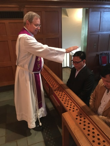 Pastor Tanney blessing the two Nepalese pastors on their confirmation day.