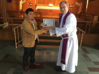 Nabin receiving his certificate of completion for Christian Doctrine.